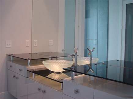 Custom mirror wall over bathroom vanity and floating glass shelves